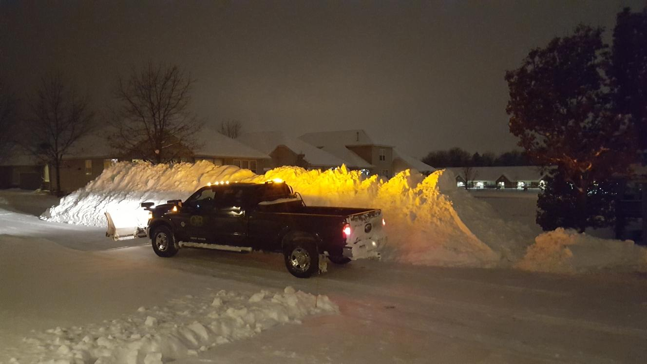 truck plowing snow at night