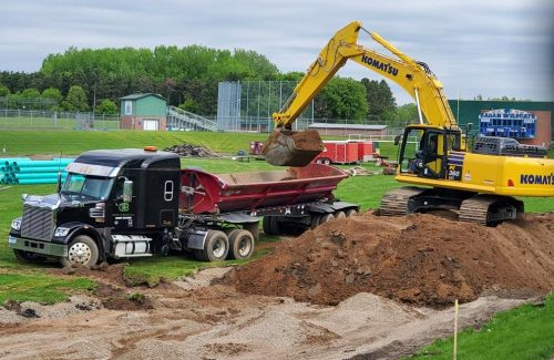 excavator moving dirt into truck