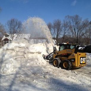 mini excavator plowing snow