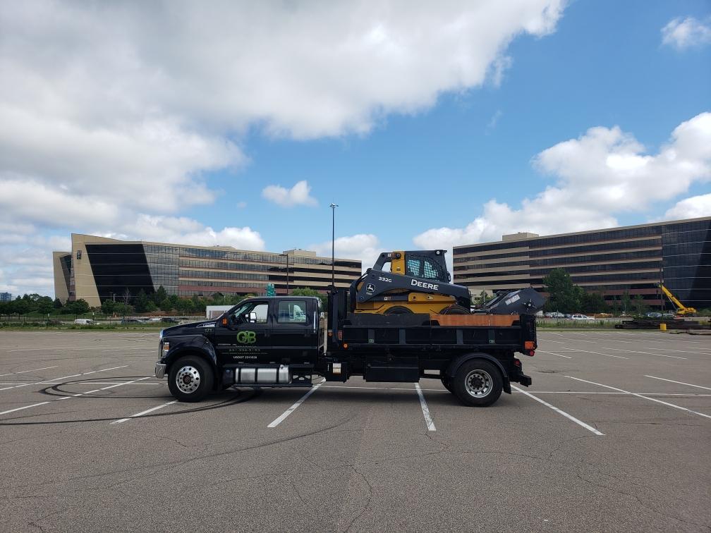 truck hauling skidloader
